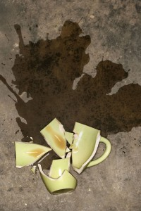 Broken coffee cup with spilled coffee on floor.